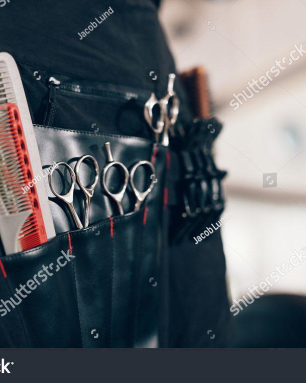 stock-photo-closeup-of-scissors-and-combs-in-a-salon-holster-pouch-hairdressing-tools-inside-a-hairdresser-684511561