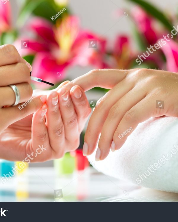 stock-photo-woman-in-a-nail-salon-receiving-a-manicure-by-a-beautician-113068372
