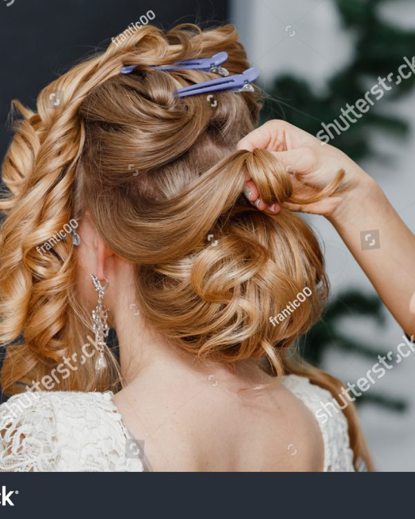 stock-photo-young-bride-getting-her-hair-done-before-wedding-by-professional-hair-stylist-548920966
